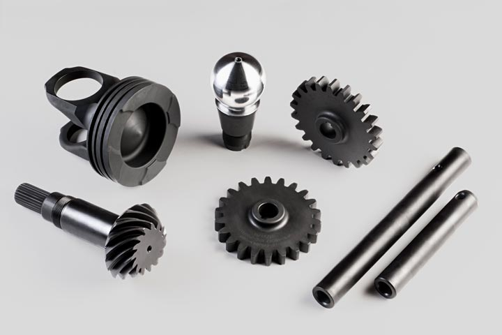 A variety of phosphate-coated metal products including gears, ball joints and rods.