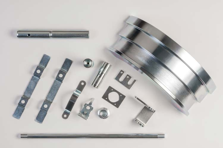 Various parts are laid out ona white background showing off their shiny new zinc plating.